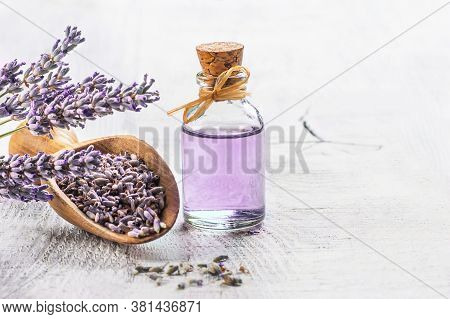 Glass Bottle Of Lavender Essential Oil With Fresh Lavender Flowers And Dried Lavender Seeds On White