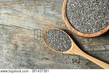 Chia Seeds ( Salvia Hispanica ) In Wooden Spoon Or Bowl On Rustic Background. Cereal Healthy Food Co