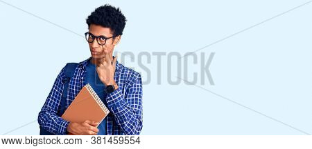Young african american man wearing student backpack holding book pointing to the eye watching you gesture, suspicious expression