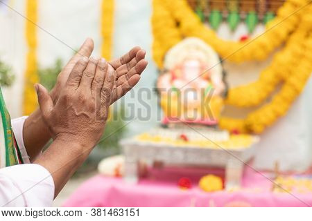 Close Up Of Elder Man Hands Offering Bhajan Or Hymn In Front Of Lord Ganesha Idol By Clapping During