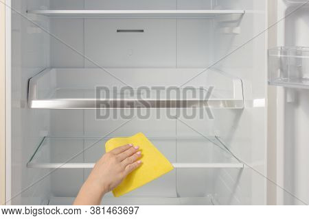Hand Cleaning Refrigerator. Person Washing Refrigerator With Rag. The Housekeeper Wipes The Shelves