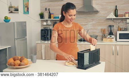 Young Woman Using Bread Toaster In The Morning For Breakfast. Housewife Using Bread Toaster For Deli