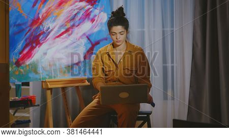 Painter Searching Inspiration On Laptop In Art Studio.