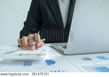 The Hands Of A Male Businesswoman Use The Calculator Are Analyzing And Calculating The Annual Income