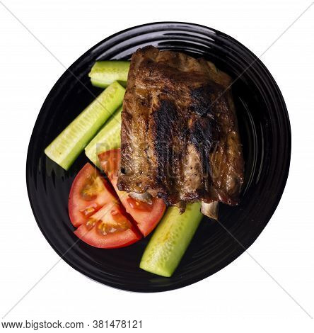 Grilled Pork Ribs With Sliced Cucumbers And Tomatoes On Black Plate. Pork Ribs Isolated On White Bac