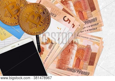 5 Belorussian Rubles Bills And Golden Bitcoins With Smartphone And Credit Cards. Cryptocurrency Inve