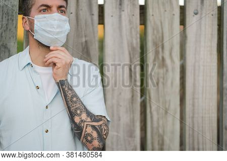 Close Up Portrait To A Young Man Wearing Medical Face Mask On An Open Air Environment. Covid19 Break