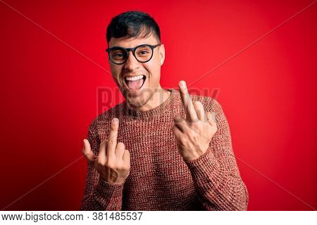 Young handsome hispanic man wearing nerd glasses over red background Showing middle finger doing bad expression, provocation and rude attitude. Screaming excited