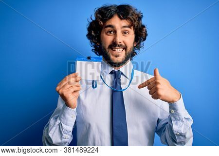 Young handsome business man with beard holding id card identification over blue background with surprise face pointing finger to himself