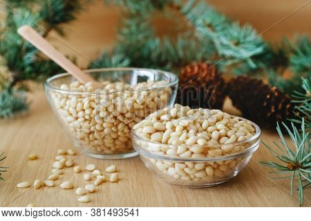 Cedar Pine Nuts In Glass Bowls With Cones, Spoon, Cedar Brunch On Wooden Background.