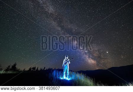 Illuminated Astronaut In White Space Suit Standing In The Middle Of Mountain Meadow Holding Guitar,