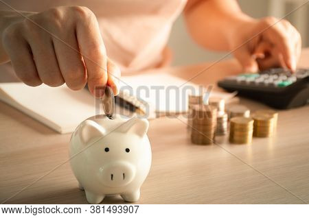 Woman Hand Putting Money Coin Into Piggy For Saving Money. Record Income And Expenses To Save Money.