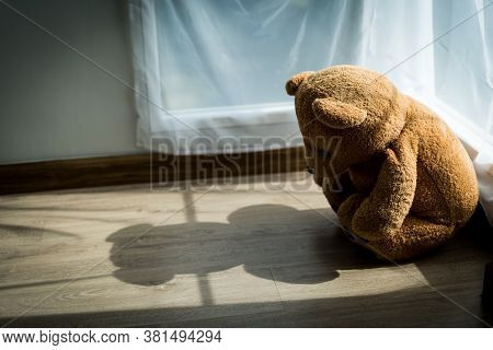 The Teddy Bear Looks Sad And Disappointed In The Corner Of The Room With Soft Sunlight Passing Throu