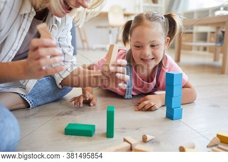 Little Girl With Down Syndrome Lying On The Floor And Watching How Her Mother Building A Tower From