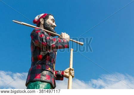 Bangor, Maine - August 27 2014: Statue of the legendary character Paul Bunyan, a mythical giant lumberjack, against blue sky on a summer day.