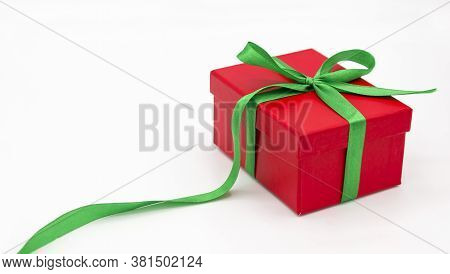 Gift Box Or Present Wrapped In Red Paper With Green Bow On White Background. Christmas Holiday Prese