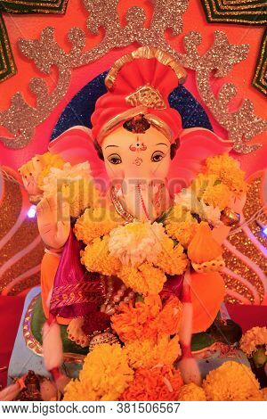 Abstract Background Of Lord Bal Ganesh Idol Pooja Worship At Home With Flowers & Modak In Hand, Gana