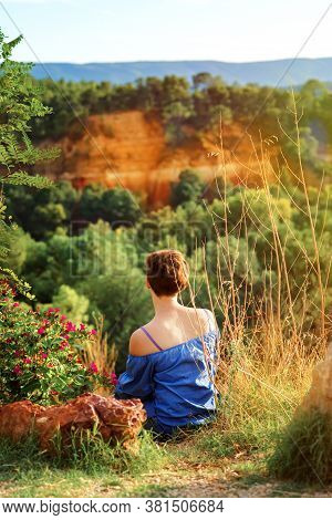 Vertical Picture Of Short Haired Girl In Blue Shirt Sitting On Top Of Hill In Sunset Time And Lookin