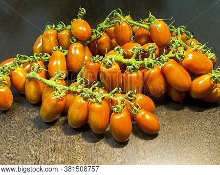 Oblong Cherry Tomatoes On The Vine Over Brown Dark Wooden Table