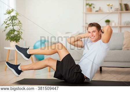 Simple Workout At Home To Keep Fit. Handsome Guy In Sportswear Doing Exercises For Press On Mat In L