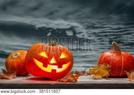October Luminous Pumpkin, Jack-lantern, Dry Leaves Against Gray Evening Sky. Background Of Wood. Hap