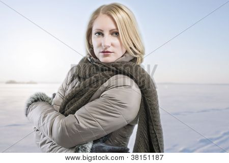 Blond Woman In Warm Clothes Over Winter Background