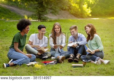 Campus Pastime. Joyful College Students Resting Outdoors With Smartphone, Sitting On Grass, Watching