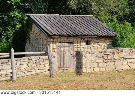 Old Rural House With Wooden Roof And Stone Walls. European Village Is Preserving Rustic Traditions A