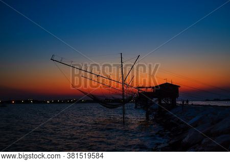 Traditional Fishing Station House With Fishnet In Water Of Adriatic Sea At Pier Diga Sottomarina, Sk