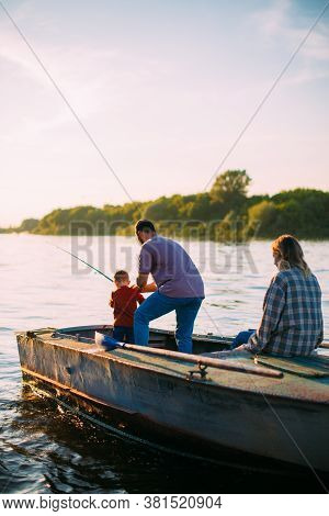 Happy Family Fishing On Boat On River In Summertime. Back View. Photography For Ad Or Blog About Fam