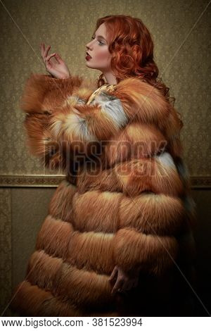 Beautiful young woman with magnificent red hair posing in a luxurious fox fur coat on a vintage background. Winter beauty fashion. Fur coat style.