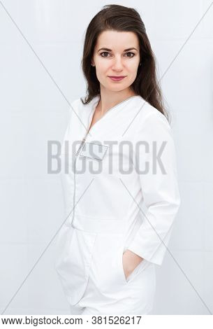 Serious Brunette Girl In A Medical Suit Posing Against A White Wall Background. The Girl Looks At Th