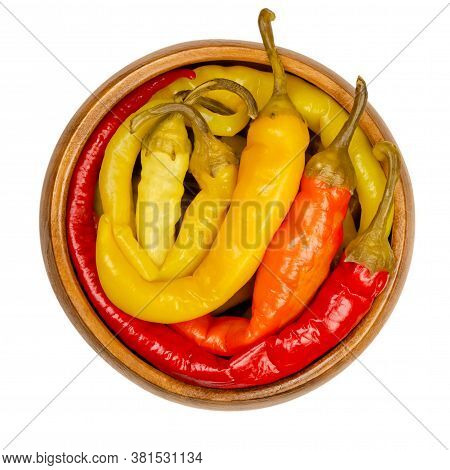 Peperoni Pickles In A Wooden Bowl. Pickled Whole Chili Peppers Of Different Bright Colors. Vegetable