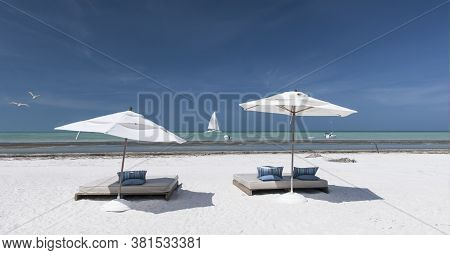 Panoramic View Of A Caribbean Beach A Few Meters From The Mexican Caribbean Ocean. Umbrellas And Sun