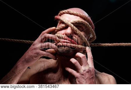 Image Of Binded Bald Man Trying Tear The Rope On Face
