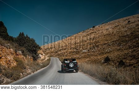 Off-Road Vehicle on Mountainous Road. 4x4 Car on the Road Trip Driving Along Lebanese Wild Landscape. Leisure Time. Active Summer Vacation.