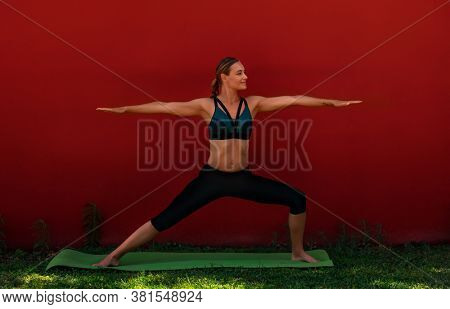 Pretty Woman Doing Yoga Exercises Outdoors. Active Young Female Standing in Virabhadrasana II. Healthy Lifestyle Concept.