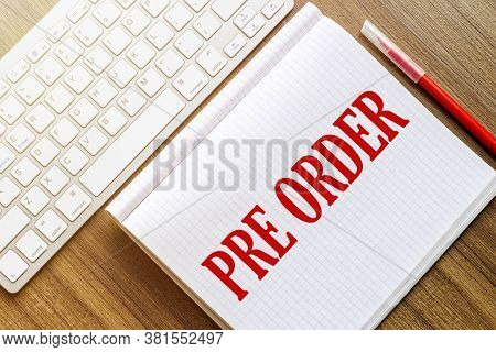 A White Notebook With The Text Pre Order Lies On A Wooden Surface Near A White Keyboard With A Red M