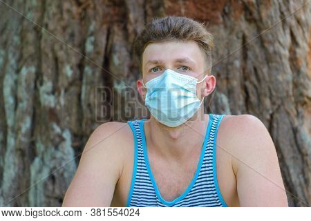 Young Man With Medical Mask On Wood Background