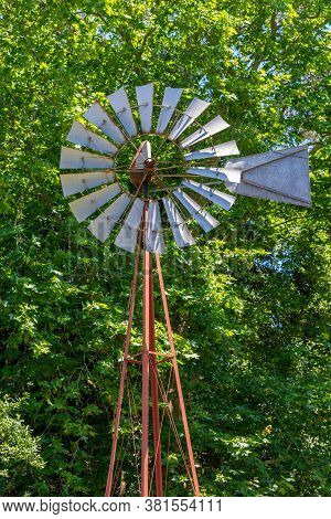 Old Water Pumping Windmill With Metal Vanes On The Background Of Green Trees