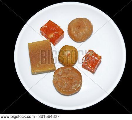 Indian Sweets Served In White Plate. Halwa, Badusha, Ghee Mysore Pak, Laddu In Decorative Plate,