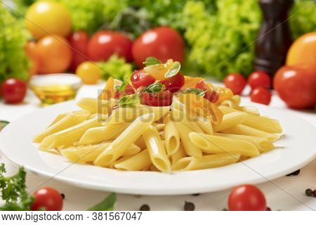 Plate Of Italian Pasta, Penne Rigate With Tomatoes And Basil