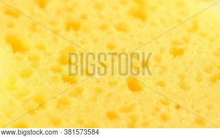 Close-up Of A Yellow Washcloth For Bathing In A Bath Or Shower. The Structure And Texture Of The Spo