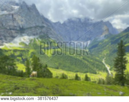 Blurred Idyllic Landscape In The Alps With Brown Cows Graze At Fresh Green Meadows, Snowcapped Mount