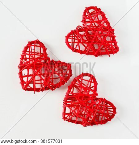 Red Handmade Hearts Made Of Twigs On A White Background. Three Red Hearts From Twigs Of Vines On A W