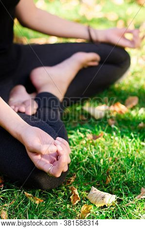 Woman Meditating And Sitting In A Cross-legged Position On The Grass. Padmasana, Lotus Pose, Hatha Y
