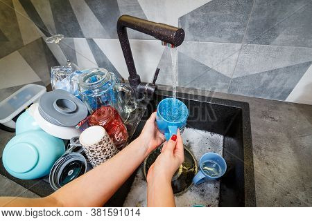 Hands With Sponge Wash The Cup Under Water, Housewife Woman In Washing Blue Mug In A Kitchen Sink Wi