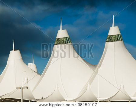 Denver International Airport at dusk with cloudy sky. poster