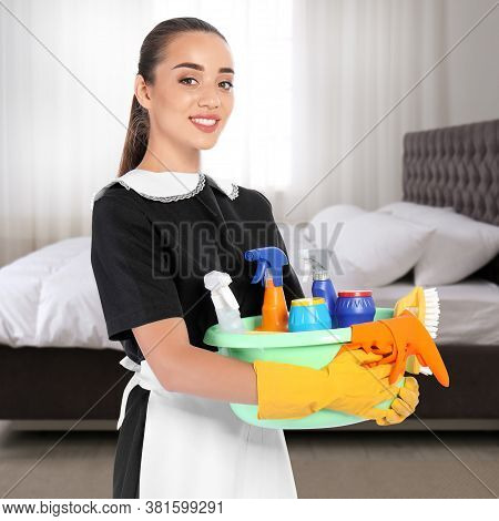 Beautiful Chambermaid With Cleaning Supplies Near Bed In Hotel Room
