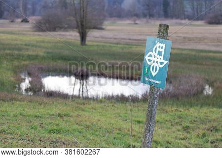German Nature Conservation Area Shield In Front Of A Moor Landscape With A Small Lake In The Backgro
